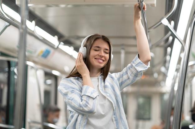 Passeggero spensierato di una ragazza carina millenaria che ascolta musica con gli auricolari wireless nel treno della metropolitana