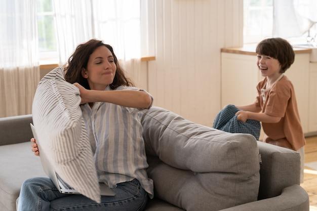 La mamma spensierata si diverte con il figlio in età prescolare in soggiorno giocando a una divertente battaglia di cuscini sul divano di casa