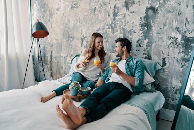 Mattinata spensierata. bella giovane coppia che fa colazione mentre trascorre il tempo a letto a casa