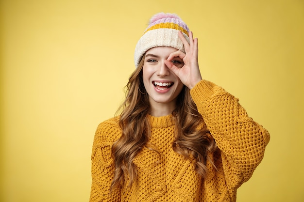 Spensierata giocosa carismatica affascinante donna caucasica vacanza invernale divertendosi spettacolo ok ok gesto guarda attraverso il cerchio ridendo felicemente sorridendo denti ampiamente bianchi, godendosi i viaggi di montagna