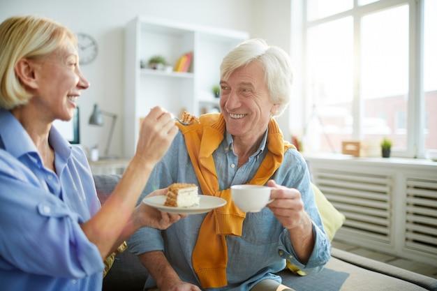 Coppie senior spensierate che godono del caffè