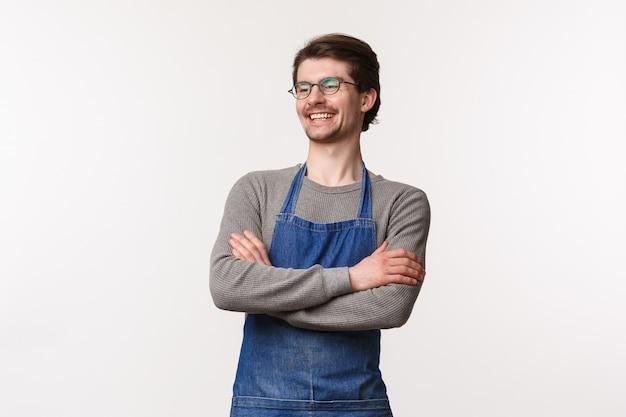 Giovane barista maschio uscente sorridente spensierato che ride con il collega che sta in grembiule con le mani ha attraversato il petto, distoglie lo sguardo felice, gestisca il proprio caffè della piccola impresa, stia su una parete bianca