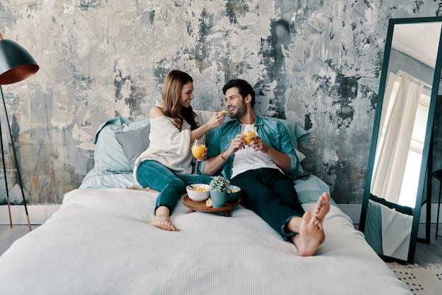 Domenica mattina spensierata. bella giovane coppia che fa colazione mentre trascorre il tempo a letto a casa