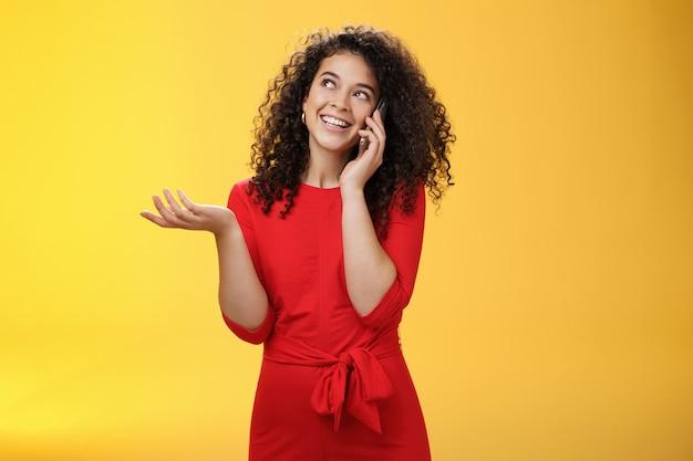 Donna carina loquace spensierata con capelli ricci in abito rosso che ha char con un amico sul telefono cellulare che tiene lo smartphone vicino all'orecchio, gesticolando mentre discute di notizie eccitanti, guardando l'angolo in alto a sinistra.