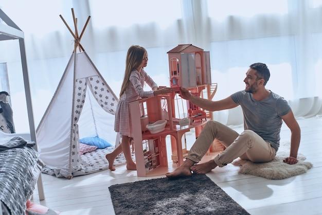 Tempo spensierato insieme. padre e figlia giocano insieme con una casa delle bambole seduti sul pavimento in camera da letto