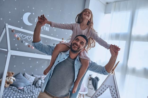 Tempo spensierato con papà. padre allegro che porta sua figlia sulle spalle e sorride mentre trascorre il tempo libero a casa