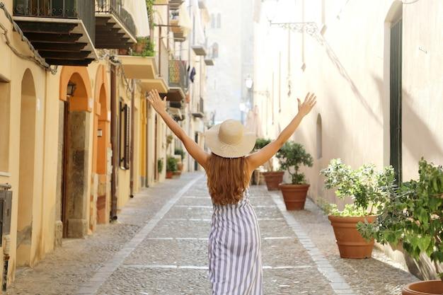 Ragazza turistica spensierata nella destinazione europea che cammina nel vicolo soleggiato.