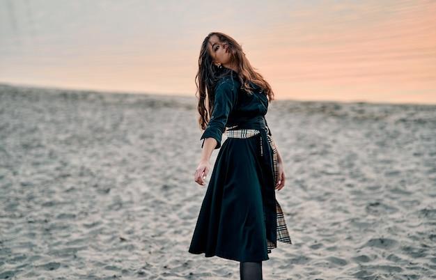Donna spensierata in abito nero e lunghi capelli ricci che ballano al tramonto sulla spiaggia. vacanze vitalità una vita sana concetto