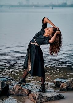 Donna spensierata in abito nero in posa al tramonto sulla spiaggia. vacanze vitalità una vita sana concetto