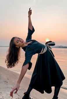 Donna spensierata che balla al tramonto sulla spiaggia. vacanze vitalità una vita sana concetto
