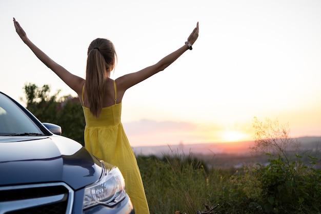 Autista donna spensierata in abito estivo giallo che si gode una calda serata vicino alla sua auto. concetto di viaggio e vacanza.