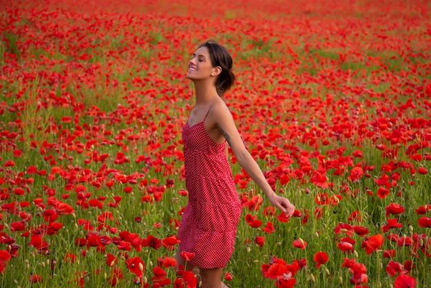 Donna spensierata nel campo dei fiori di papavero. femmina di pianta botanica di fiori di campo. giorno dell'anzac.