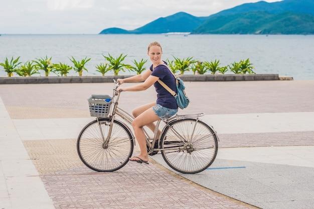 Donna spensierata con la bicicletta in riva al mare divertendosi e sorridendo.