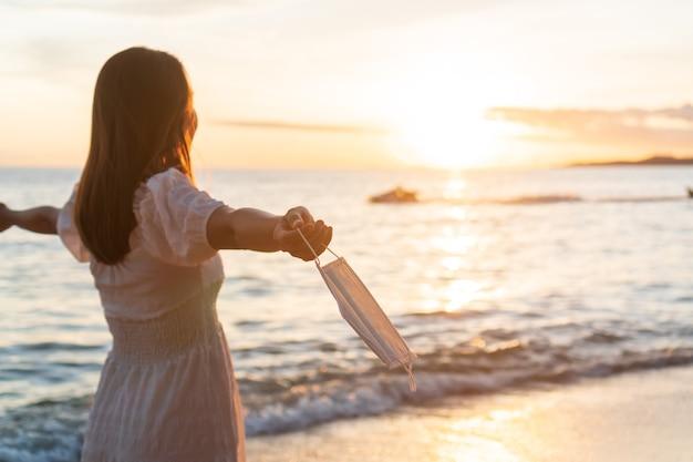 Spensierata giovane donna asiatica viaggiatore togliersi la maschera protettiva e tenendo sulla sua mano