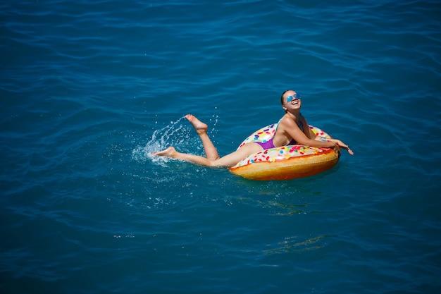 Spensierata giovane donna che si gode una giornata rilassante in mare, galleggiando su un anello gonfiabile, vista dall'alto. concetto di vacanza al mare
