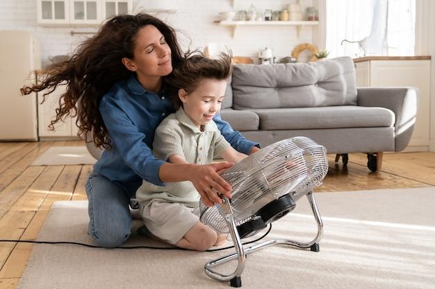 La giovane mamma o la tata spensierata si divertono con il figlio maschio a casa seduti insieme al grande ventilatore che soffia aria