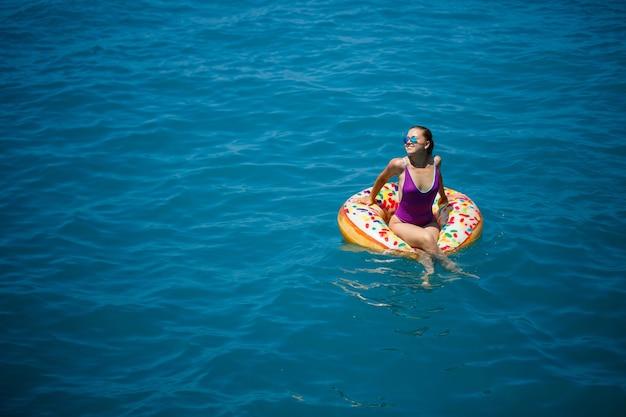 Giovane donna spensierata che si gode una giornata di relax in mare, galleggiando su un anello gonfiabile. concetto di vacanza al mare. messa a fuoco selettiva