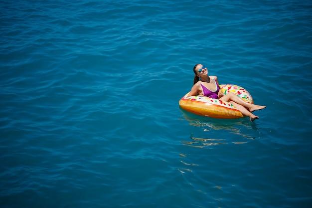 Giovane donna spensierata che si gode una giornata di relax in mare, galleggiando su un anello gonfiabile. concetto di vacanza al mare