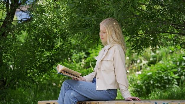 Spensierata giovane donna che legge un romanzo affascinante mentre è seduta su una panchina del parco. amore per i libri, attività ricreative all'aperto. 4k uhd
