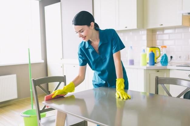 Detergente attento e simpatico sta a tavola e lo pulisce