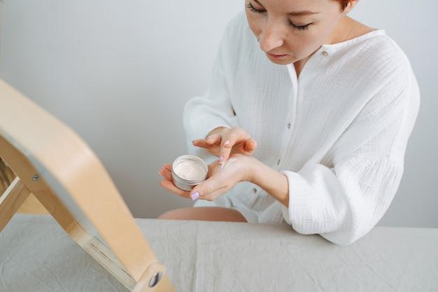 Attenta donna dai capelli corti che si applica il correttore sul polso, osservando la reazione cutanea. utilizzo di prodotti e cose eco-compatibili. seduto davanti allo specchio.