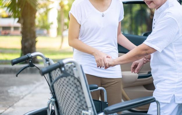 Badante che aiuta una donna asiatica disabile anziana dalla sedia a rotelle a salire in macchina