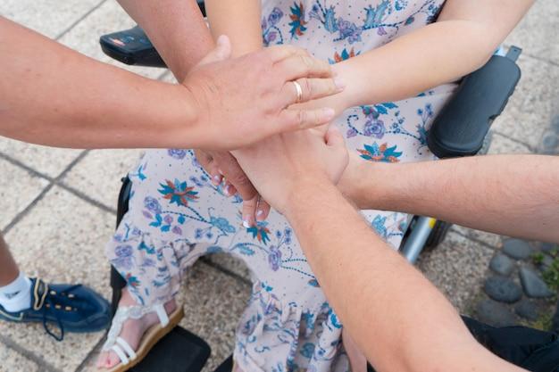 Caregiver, assistenza specializzata, badante mani mano nella mano di donna diabetica in sedia a rotelle.