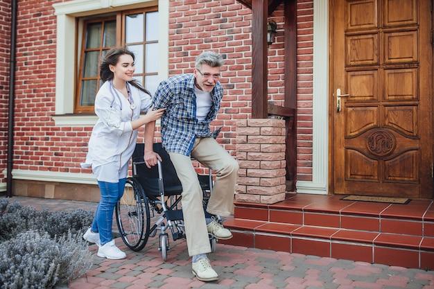 Badante che sostiene uomo senior disabile felice in una sedia a rotelle nell'ospedale.