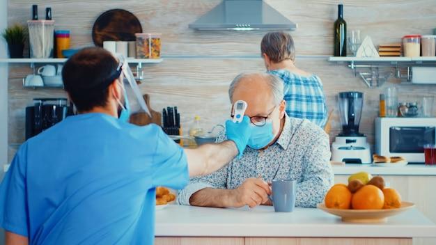Badante che utilizza un termometro a infrarossi per misurare la temperatura dell'uomo anziano in cucina durante l'epidemia di coronavirus. assistente sociale che controlla le persone vulnerabili per la prevenzione della diffusione della malattia