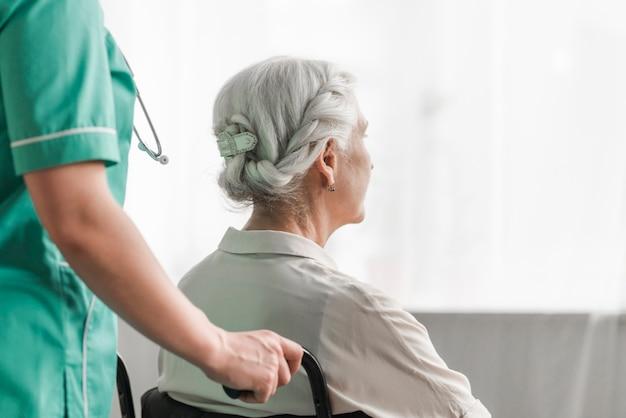 Badante con paziente femminile anziano in sedia a rotelle