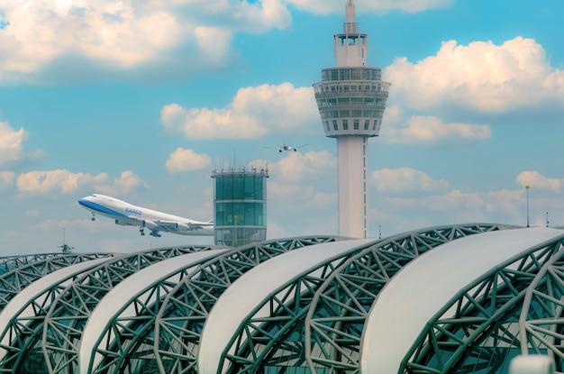 Aereo da carico che vola sopra l'edificio dell'aeroporto. aereo merci. concetto di logistica aerea. attività di carico e spedizione. trasporto merci. l'edificio dell'aeroporto con cielo azzurro e cumuli bianchi.