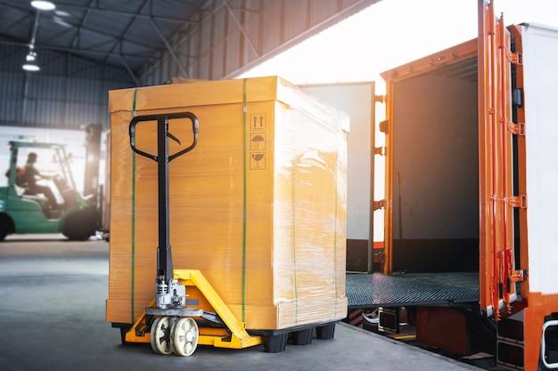 La scatola di carico con il transpallet manuale sta caricando in una logistica del magazzino di consegna della spedizione di container