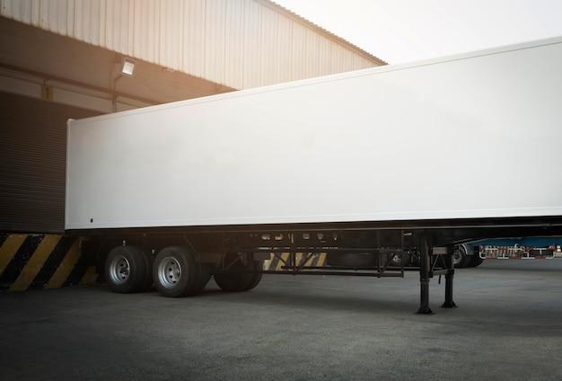 Caricamento del camion del contenitore di carico al magazzino del bacino. stazioni di attracco per rimorchi. trasporto su camion di merci industriali.