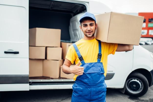 Industria di consegna del carico, lavoratore maschio in uniforme mostra il pollice in su. contenitore vuoto