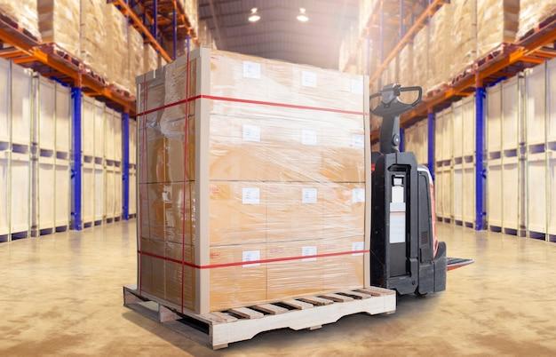 Spedizione di pallet da carico e transpallet elettrico con carrello elevatore nello stoccaggio del magazzino.