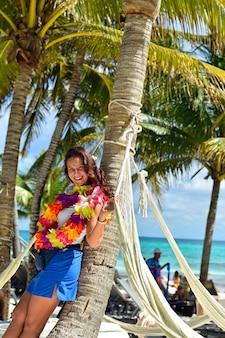 Ragazza caraibica in vacanza appoggiata a una palma che indossa una collana floreale