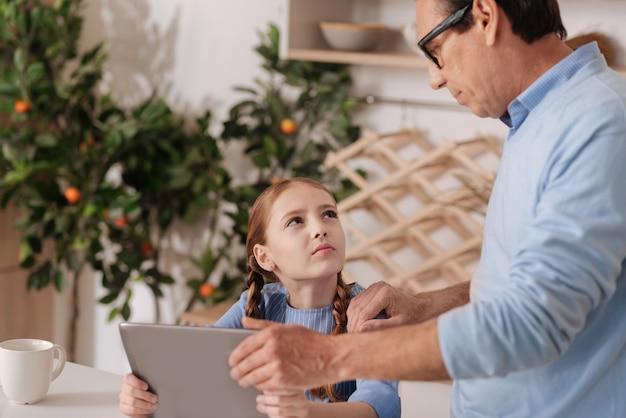 Prendersi cura dell'invecchiamento fiducioso nonno in piedi a casa mentre porta via il dispositivo digitale dalla nipote e dall'educazione del ragazzino