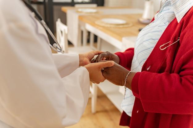 Badante premuroso. donna dalla pelle scura che indossa un braccialetto e un cardigan rosso che stringe la mano alla sua premurosa badante