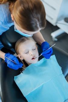 Donna premurosa che controlla i denti superiori del suo piccolo paziente sdraiato su una sedia da dentista con gli occhi chiusi