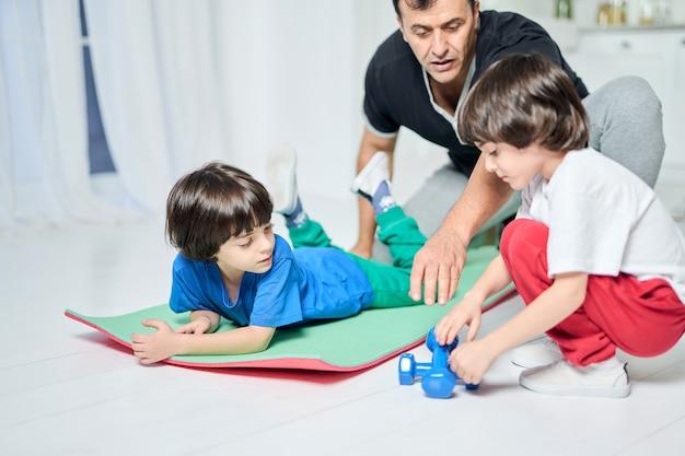 Padre ispanico premuroso che trascorre del tempo con i suoi due ragazzini, facendo allenamento insieme mentre è seduto su un tappetino all'interno della casa. paternità, sport, concetto di educazione