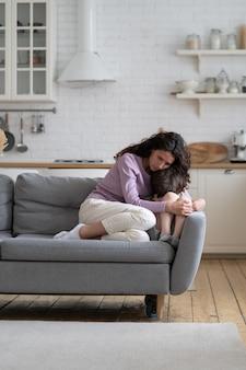 La mamma premurosa abbraccia il bambino offeso che piange dopo l'abuso preoccupato giovane mamma abbraccia un ragazzo in età prescolare stressato