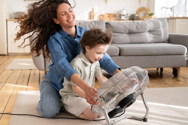 La mamma premurosa si rilassa si diverte con il bambino a casa seduto a ridere insieme al figlio davanti al ventilatore