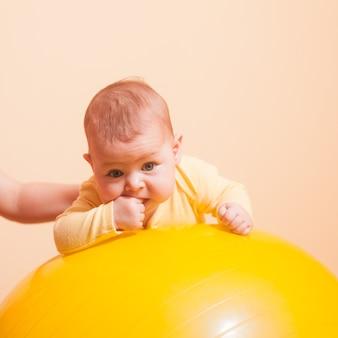 Madre premurosa che fa esercizi sportivi con il suo bambino su fitball