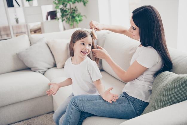 La madre premurosa fa la sua piccola figlia pettinatura in casa