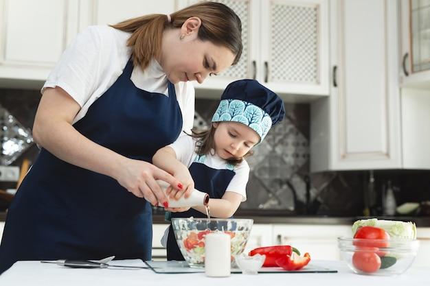 La madre premurosa insegna alla sua piccola figlia come preparare un'insalata in cucina