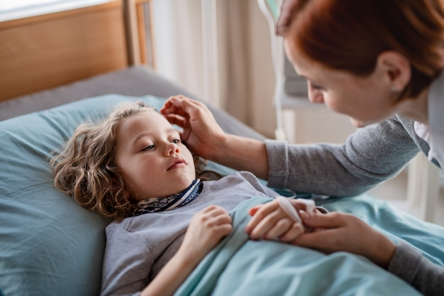 Una madre premurosa che visita la figlia di una bambina a letto in ospedale.