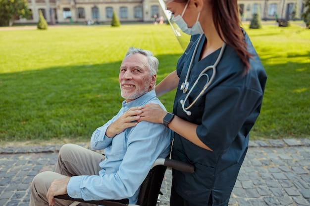 Infermiera premurosa che indossa visiera e maschera durante una passeggiata con un uomo anziano che sta recuperando un paziente in a