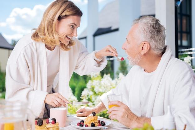 Moglie premurosa. raggiante casalinga attraente che si prende cura di suo marito durante la colazione mentre gli dà un po 'di lampone
