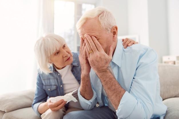 Moglie premurosa. piccola donna anziana che tiene un fazzoletto e accarezza i mariti indietro, cercando di consolarlo, mentre piange