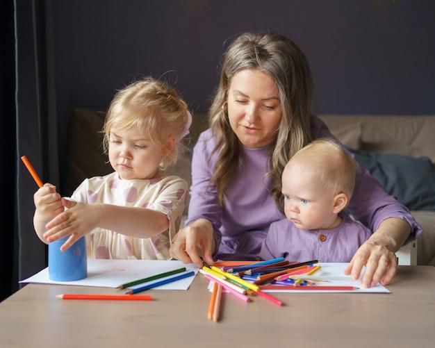 Giovane mamma premurosa che insegna come disegnare i suoi due bambini piccoli
